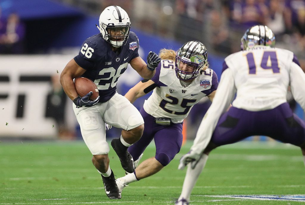 GLENDALE, AZ - DECEMBER 30:  Running back Saquon Barkley #26 of the Penn State Nittany Lions rushes the football past linebacker Ben Burr-Kirven #25 of the Washington Huskies during the first half of the Playstation Fiesta Bowl at University of Phoenix Stadium on December 30, 2017 in Glendale, Arizona.  (Photo by Christian Petersen/Getty Images)