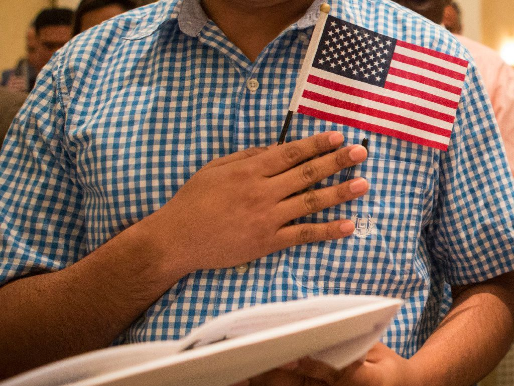 Sanjit Dhakal, from Nepal, places his hand and flag over his heart as he recites the Pledge of Allegiance during a naturalization ceremony on June 29, 2017, at the Belo Mansion in Dallas.