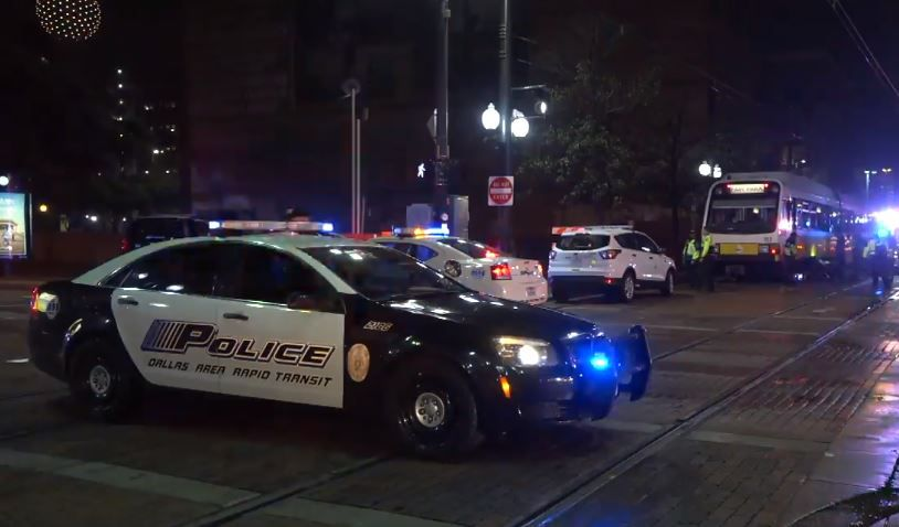 Dallas Area Rapid Transit police block off streets near where someone became trapped under a DART train Wednesday night in Downtown Dallas.