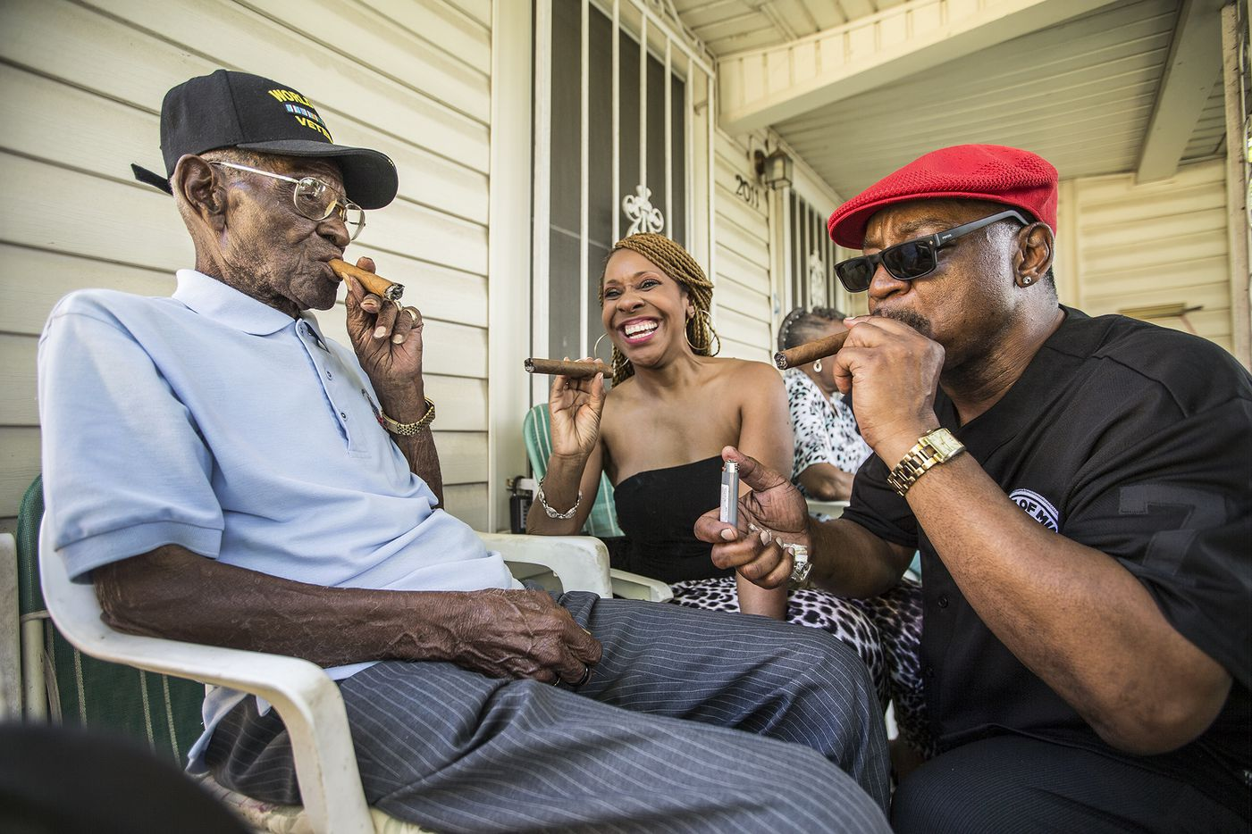 Richard Overton (left) smokes a cigar with neighborhood friends Donna Shorts (center) and Martin Wilford in May 2015, in Austin, when Overton was 109. Wilford says that he has known Overton for 37 years and he looks at Mr. Overton as if he were his biological father.