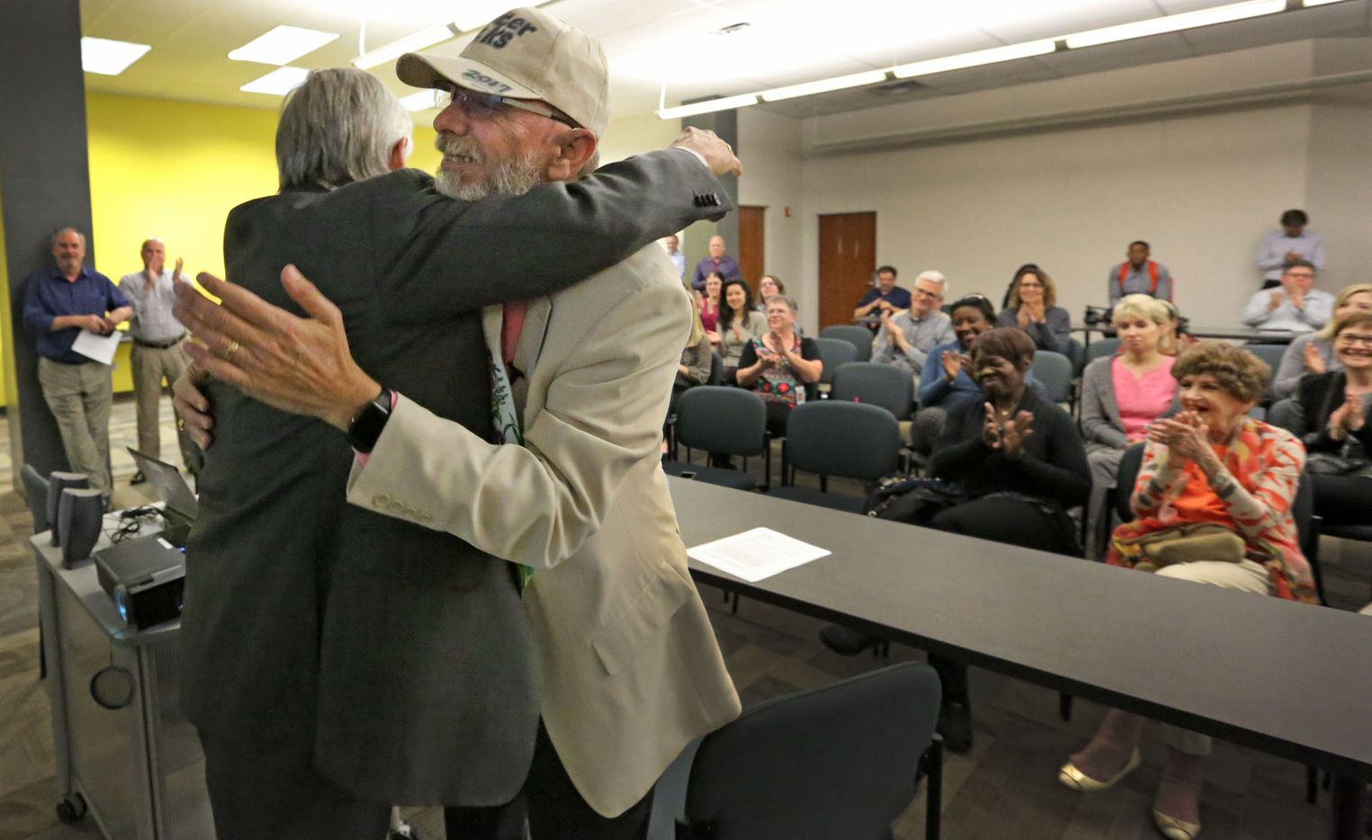Chairman, president and CEO of A. H. Belo Corporation Jim Moroney, left, hugs Jeffrey Weiss at the reporter's career tribute party at The Dallas Morning News on Wednesday, March 1, 2017. (Louis DeLuca/The Dallas Morning News)