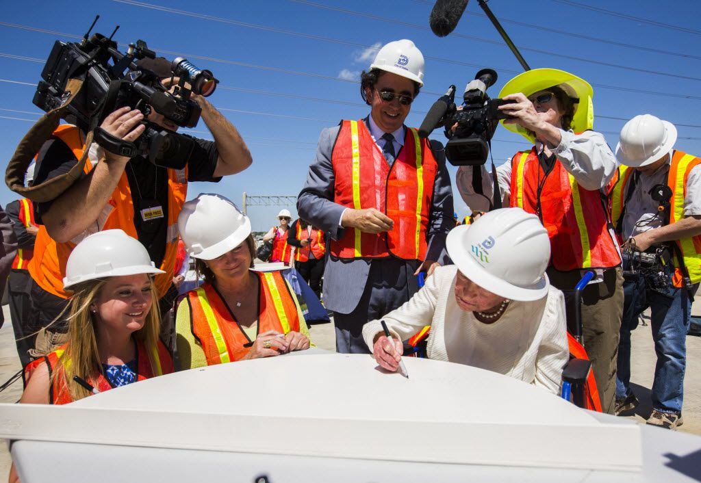 Margaret McDermott, right, signs a piece of the Margaret McDermott Bridge, which was named after her, flanked by Grace Cook, McDermott's granddaughter, left; Mary McDermott Cook, daughter of McDermott, and architect Santiago Calatrava during a bridge signing ceremony on June 11, 2015 in Dallas.