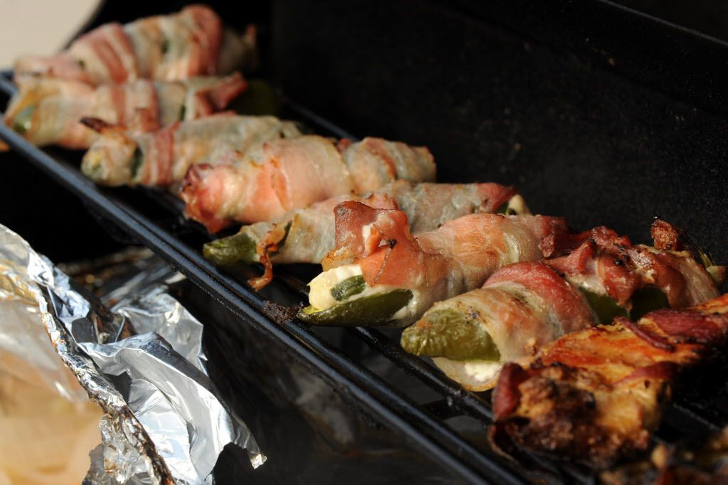 Bacon wrapped stuffed jalapenos sizzle on the grill at the Jimmy Buffett tailgate party at Toyota Stadium in Frisco, TX on May 30, 2015.
