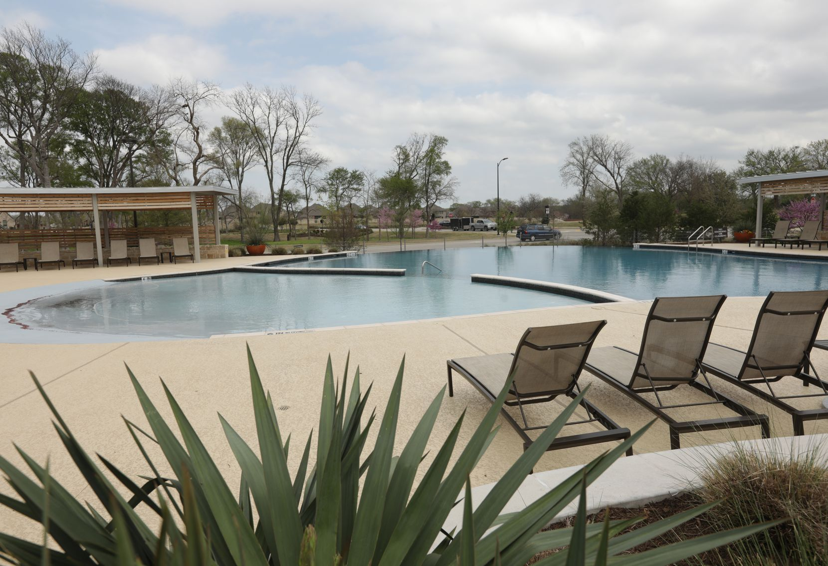 The Trinity Falls community of new homes includes a pool and lounging area.