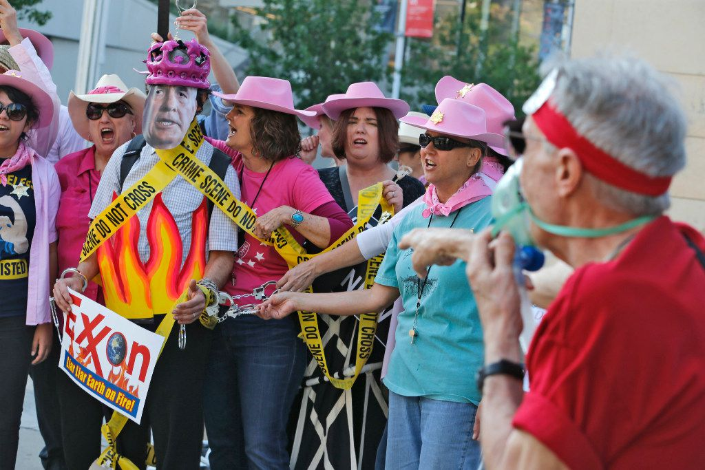 Members of Code Pink, including Danna Miller Pyke (right of fake Rex Tillerson), picket and stage a mock arrest of Tillerson (Ernest Jones) as protesters gather outside of the Exxon shareholders meeting across the street from Morton H. Meyerson Symphony Center in Dallas on May 31, 2017.