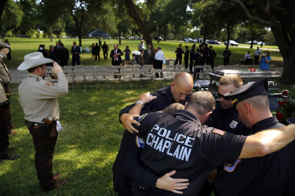Millville (New Jersey) police chaplain Robert Ossler (center) prays with (from his left) Middletown (Connecticut) police officer Ryan Jeffries, North Brunswick (New Jersey officers Joe Grasso, Ryan Uzunis, and Brian Hoiberg following the graveside service for slain Dallas police Sgt. Michael Smith at the Restland Funeral Home and Cemetery in Dallas, Thursday, July 14, 2016. Smith was gunned down in an ambush attack in downtown Dallas a week ago. Four Dallas police officers and one DART officer were killed. (Tom Fox/The Dallas Morning News)