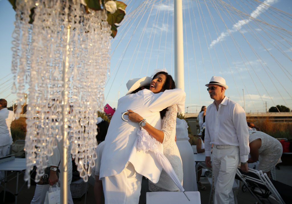 Bebe Walder gets a hug from Paul Raehpour during the inaugural Diner en Blanc Dallas on the Continental Avenue Bridge in Dallas on Sept. 17, 2015. Exactly 1,678 people attended the event, which requires dinner guests to dress all in white and bring their own tables, chairs and centerpieces. As per tradition, the location was kept private leading up to the event.