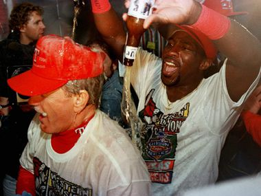 ORG XMIT: ARL107 Texas Rangers manager Johnny Oates, left, is doused by player Mark McLemore, right, as the celebrate the Rangers' American League West Championship Saturday morning Sept. 28, 1996, in the team lockerroom.  (AP Photo/Eric Gay)