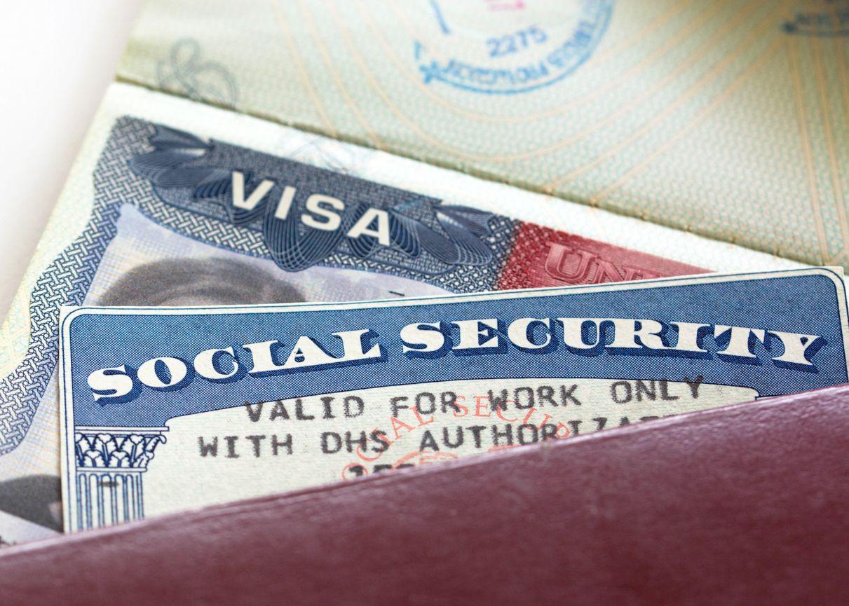 Una tarjeta del Seguro Social junto a una visa de autorización migratoria. iStock.