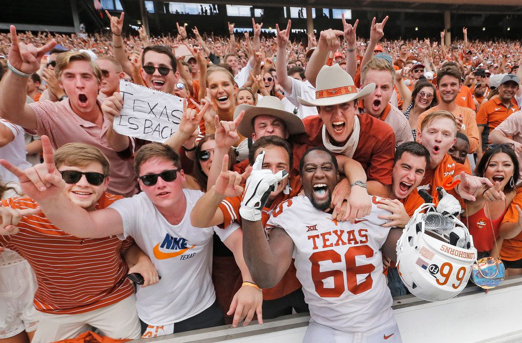 Texas Longhorns offensive lineman Calvin Anderson (66) celebrates with fans after the Longhorns 48-45 win during the University of Texas Longhorns vs. the Oklahoma Sooners NCAA football game at the Cotton Bowl in Dallas on Saturday, October 6, 2018. (Louis DeLuca/The Dallas Morning News)