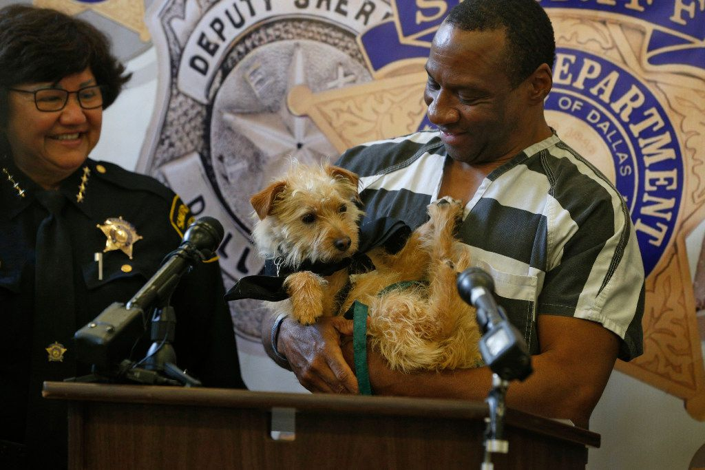 "Dallas County Sheriff Lupe Valdez (left) looks on as Thomas Chambers holds the dog ""Dallas"" during a press conference about inmates training dogs as part of a new job skills/empathy-boosting program at Kays Tower Jail in Dallas on March 29, 2017."