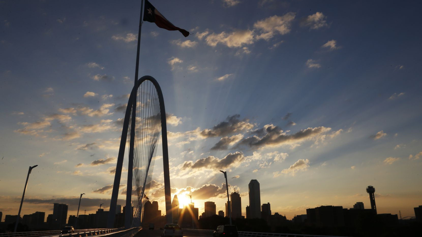 The sun emerges over the Dallas skyline with the Margaret Hunt Hill Bridge  in the foreground on Aug. 12, 2014, in Dallas.