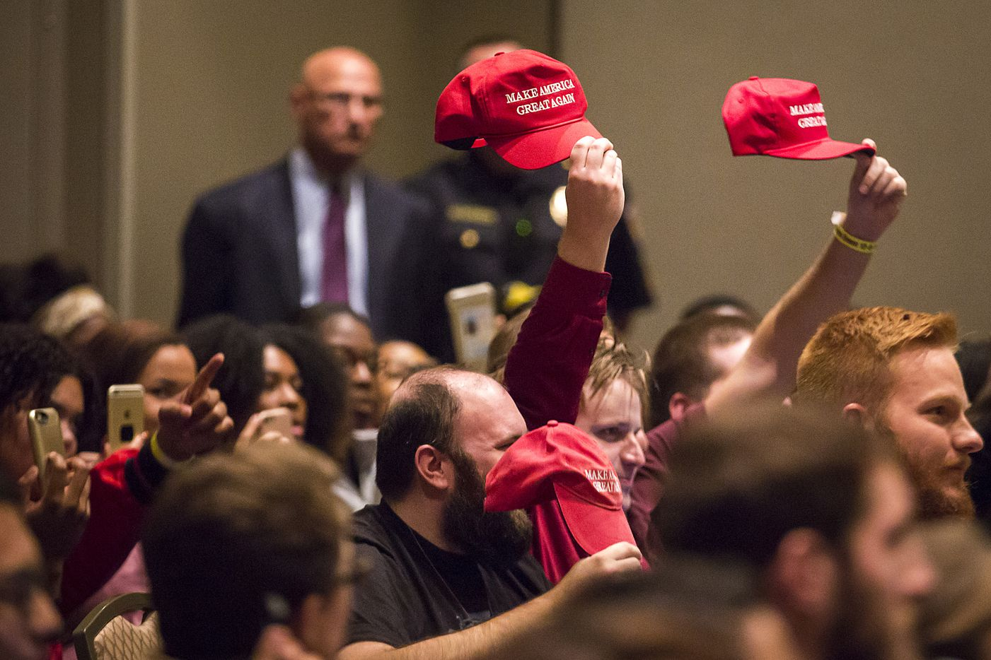 "Supporters hold up Donald Trump ""Make America Great Again"" hats as Richard Spencer speaks."