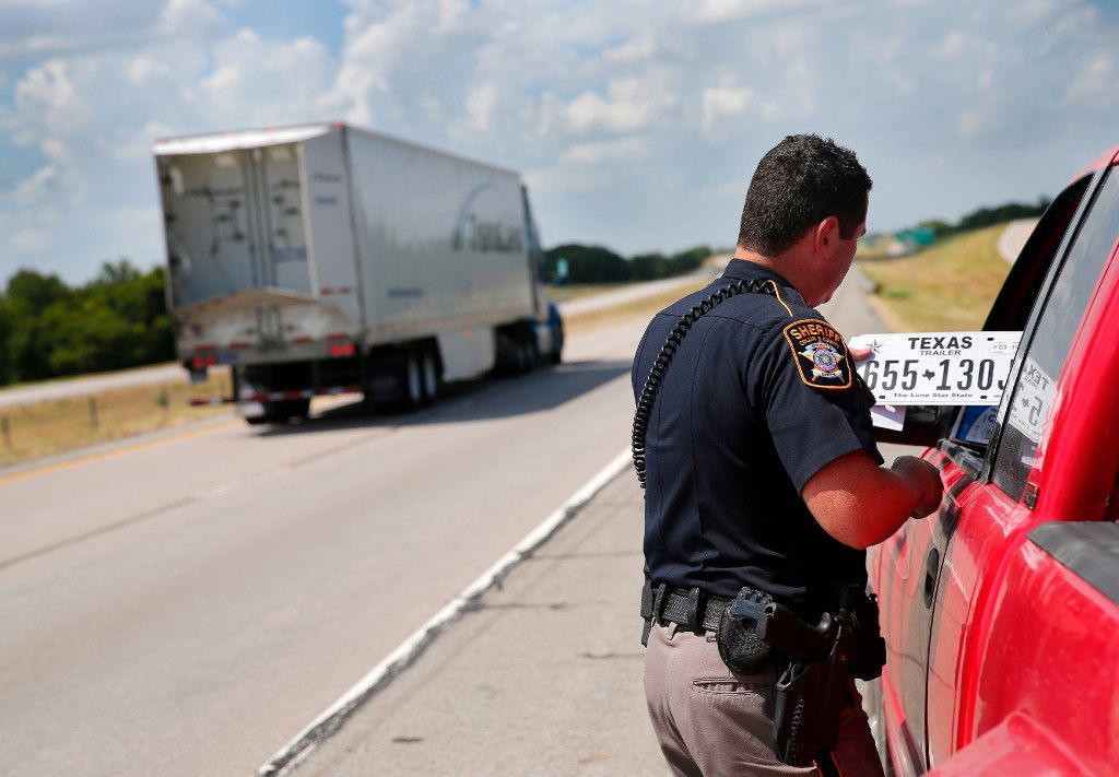 Collin County Sheriff's Deputy Rodney Tackett examines the trailer plate that should have been mounted to a trailer as he made a stop on U.S. Highway 75 in Collin County on Tuesday. The driver got a warning.