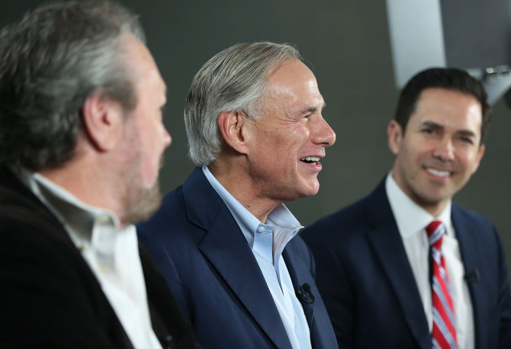 Gov. Greg Abbott speaks alongside WBAP radio host Rick Roberts (left) and Alex Trevino (right), his campaign spokesperson, on Facebook live after clinching the Republican nomination for governor Tuesday at the DoubleTree Hotel in Farmers Branch.