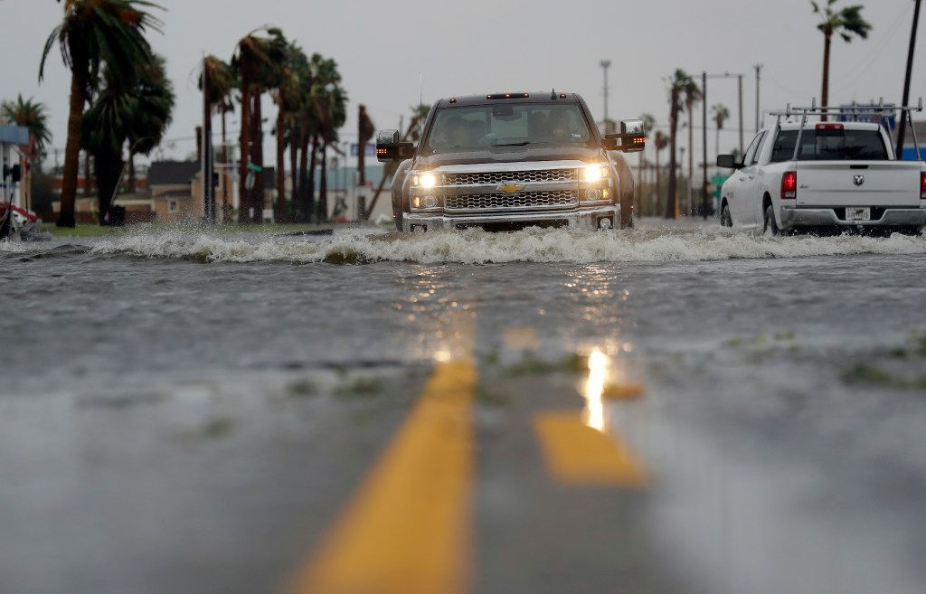A drives moves through flood waters left behind by Hurricane Harvey, Saturday, Aug. 26, 2017, in Aransas Pass, Texas.   Harvey rolled over the Texas Gulf Coast on Saturday, smashing homes and businesses and lashing the shore with wind and rain so intense that drivers were forced off the road because they could not see in front of them.