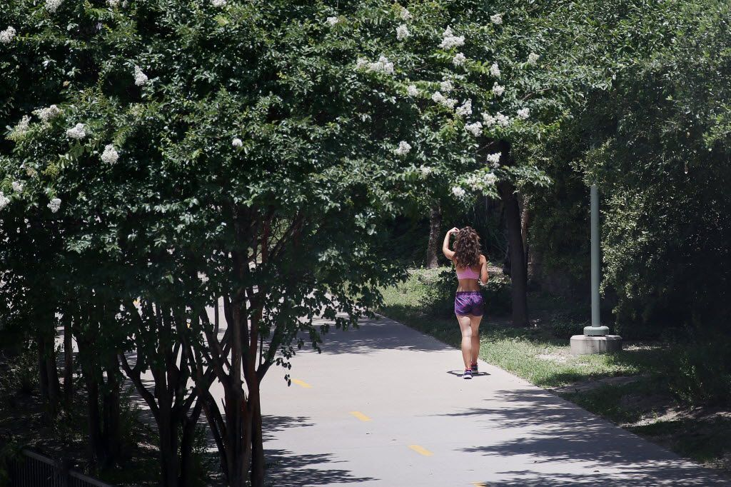 A pedestrian walks along the Katy Trail near the trail's southern terminus north of the American Airlines Center in the Victory Park area of Dallas Tuesday June 22, 2016.