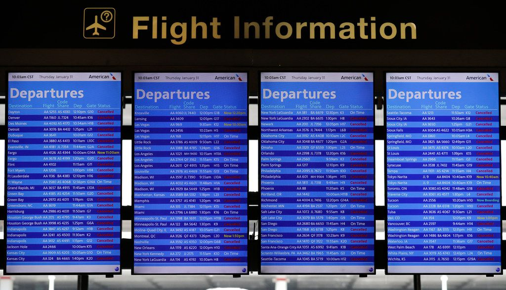 Flight information screens show flight status information at O'Hare International Airport in Chicago.