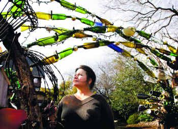 Barbara Dybala, under a bottle arch in her Sunnyvale yard, has been making mosaic garden orbs for three years. The artist took up mosaics 10 years ago.