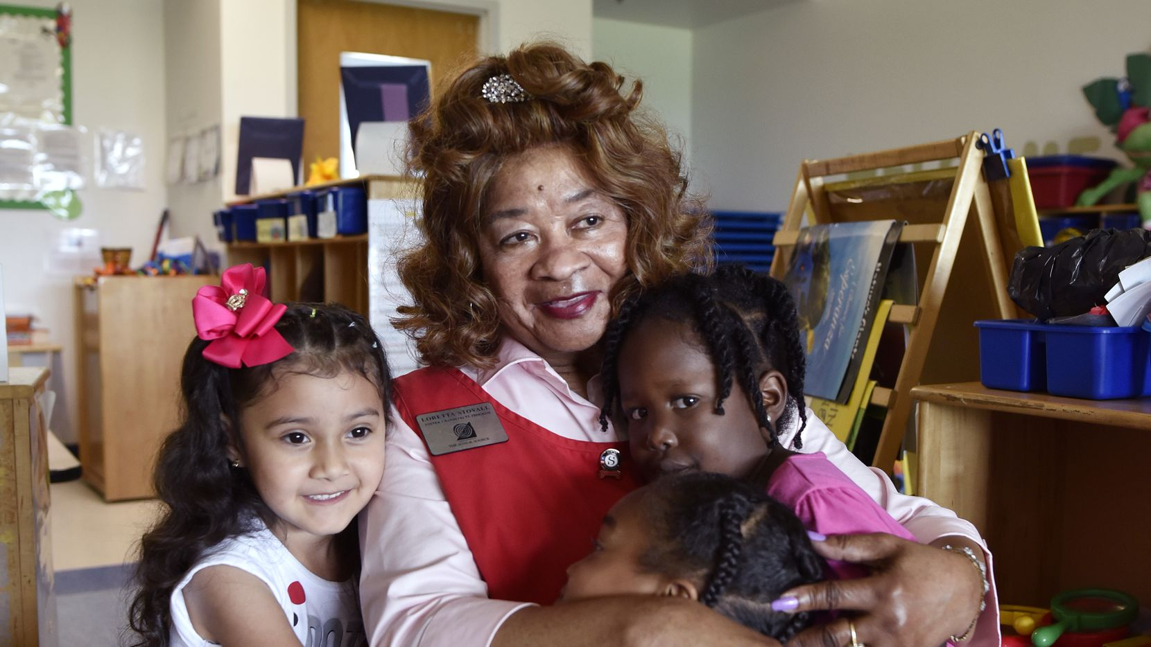 Foster grandparent Loretta Stovall, 84, gets goodbye hugs as she reaches the end of her day at the Wanda Meshack Smith Head Start Center in Dallas.
