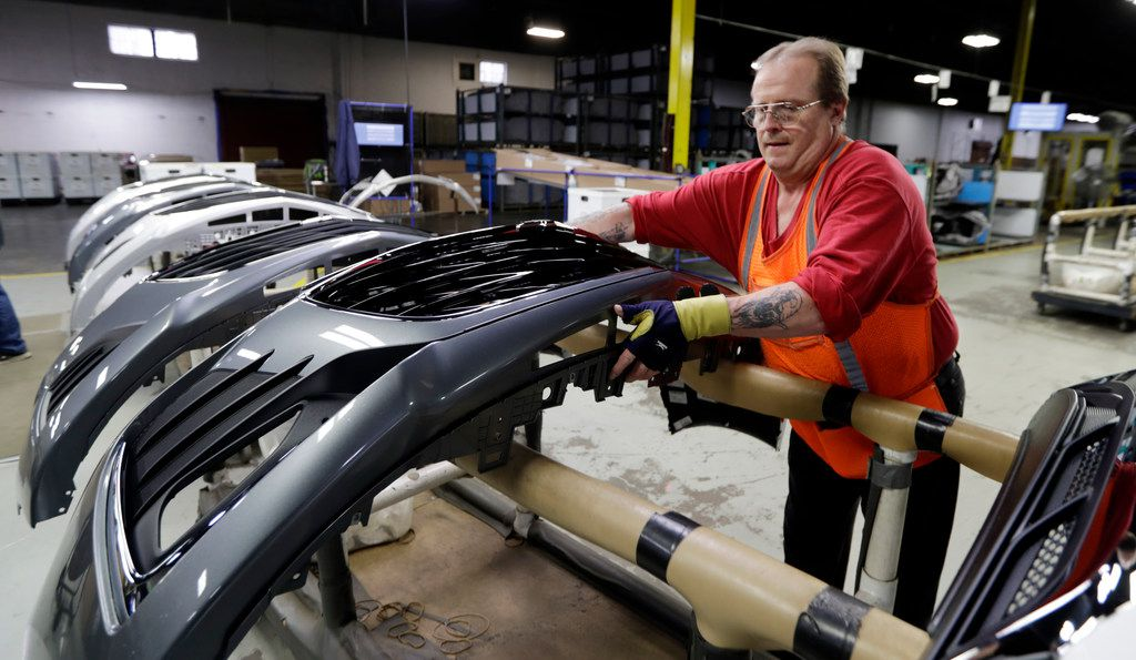 Clifford Goff, a bezel assembler, transfers a front end of a General Motors Chevrolet Cruze during assembly at Jamestown Industries, Wednesday, Nov. 28, 2018, in Youngstown, Ohio. Jamestown Industries supplies parts for the Chevy Cruze. GM said Monday that Lordstown will stop making the Chevy Cruze by March, at a cost of 1,400 union jobs on top of the 2,700 lost there since President Donald Trump took office. (AP Photo/Tony Dejak)