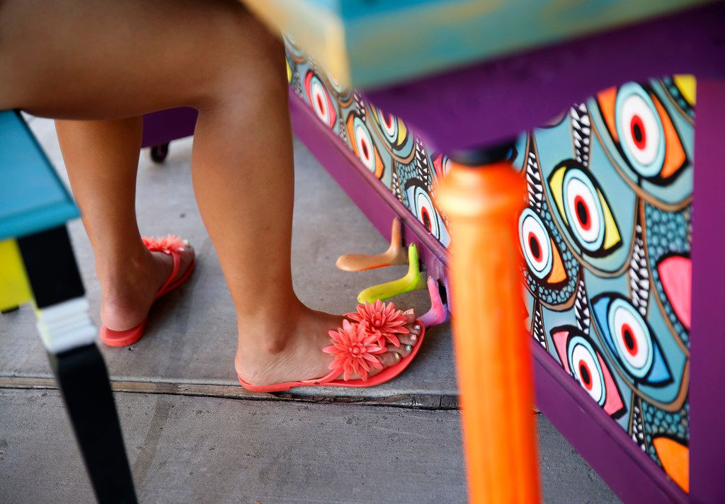 """Sunny Yun, a UNT music doctoral student, works the foot pedal as she plays on artist Leigha Lugo's painted piano in the Dallas Farmers Market on July 14, 2018. Lugo was commissioned to paint pianos in a fashion that captures the spirit of Dallas art and music. """"Play On, Dallas"""" is a project by the Dallas Office of Cultural Affairs."""