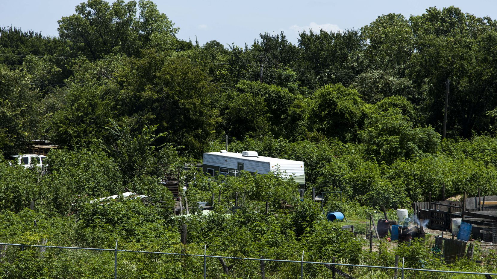 A mobile home sits amid thick vegetation in Sandbranch, a small unincorporated Dallas County community that lacks potable water. The community is not connected to Dallas' water supply.