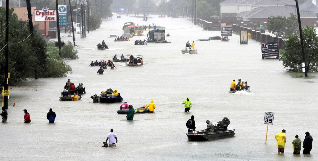 In this Aug. 28 photo, rescue boats fill a flooded street as flood victims are evacuated as floodwaters from Tropical Storm Harvey rise in Houston.
