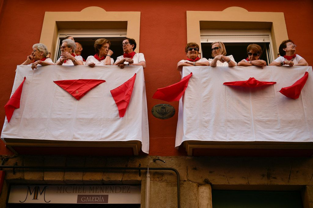 People dressed in a red and white wait to see the San Fermin religious figure from a balcony during the procession at the San Fermin Festival.