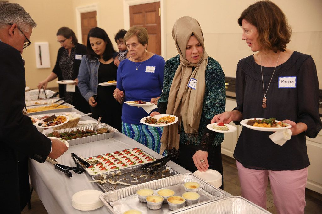 Kirsten Granberry (right) speaks with Zainab Aktepe (second to right) while making their plates during an interfaith Ramadan dinner with members of the Dialogue Institute and Wilshire Baptist Church at the church in Dallas on June 7, 2018. Guests broke the Ramadan fast after Emrah Aktepe, who is director of the Dialogue Institute Dallas, explained Ramadan.