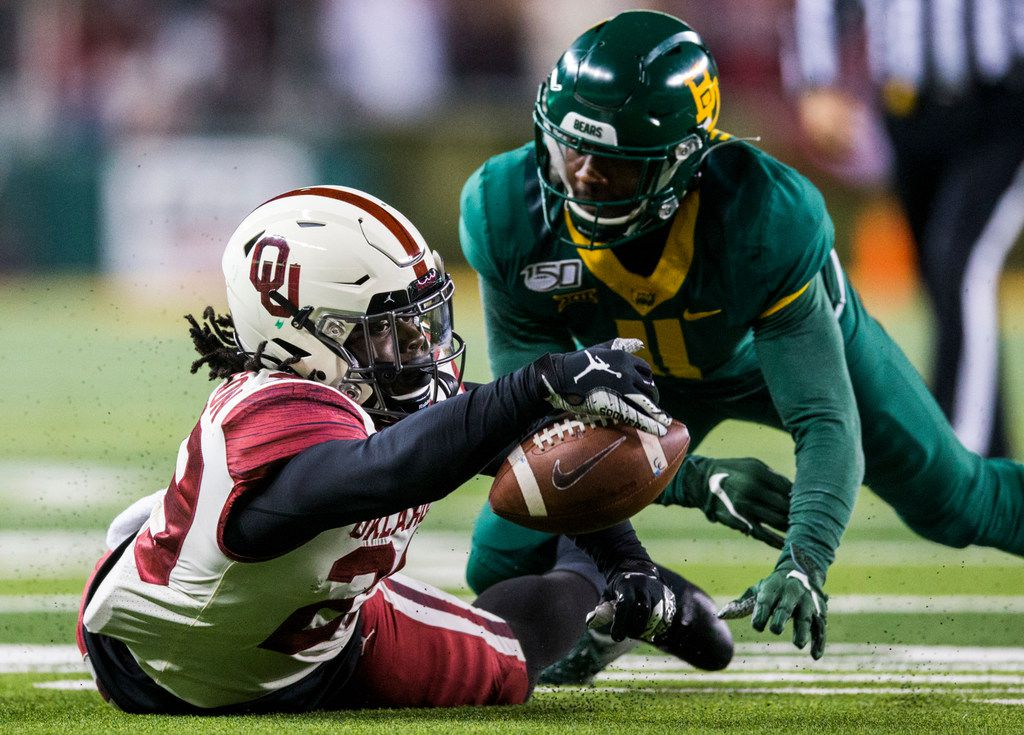Oklahoma Sooners running back Rhamondre Stevenson (29) recovers his own fumble near Baylor Bears cornerback Jameson Houston (11) during the third quarter  of an NCAA football game between Baylor University and Oklahoma University on Saturday, November 16, 2019 at McLane Stadium in Waco, Texas. (Ashley Landis/The Dallas Morning News)