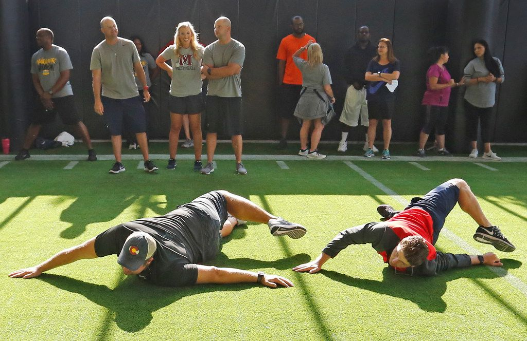 Frisco Centennial teachers JD Walton, left and Stephen Young  practice a stretch as Frisco ISD physical education teachers learn new warm-up routines for elementary, middle and high school students from professionals at the Baylor Scott & White Sports Performance Center at the Star in Frisco on Thursday. (Louis DeLuca/The Dallas Morning News)