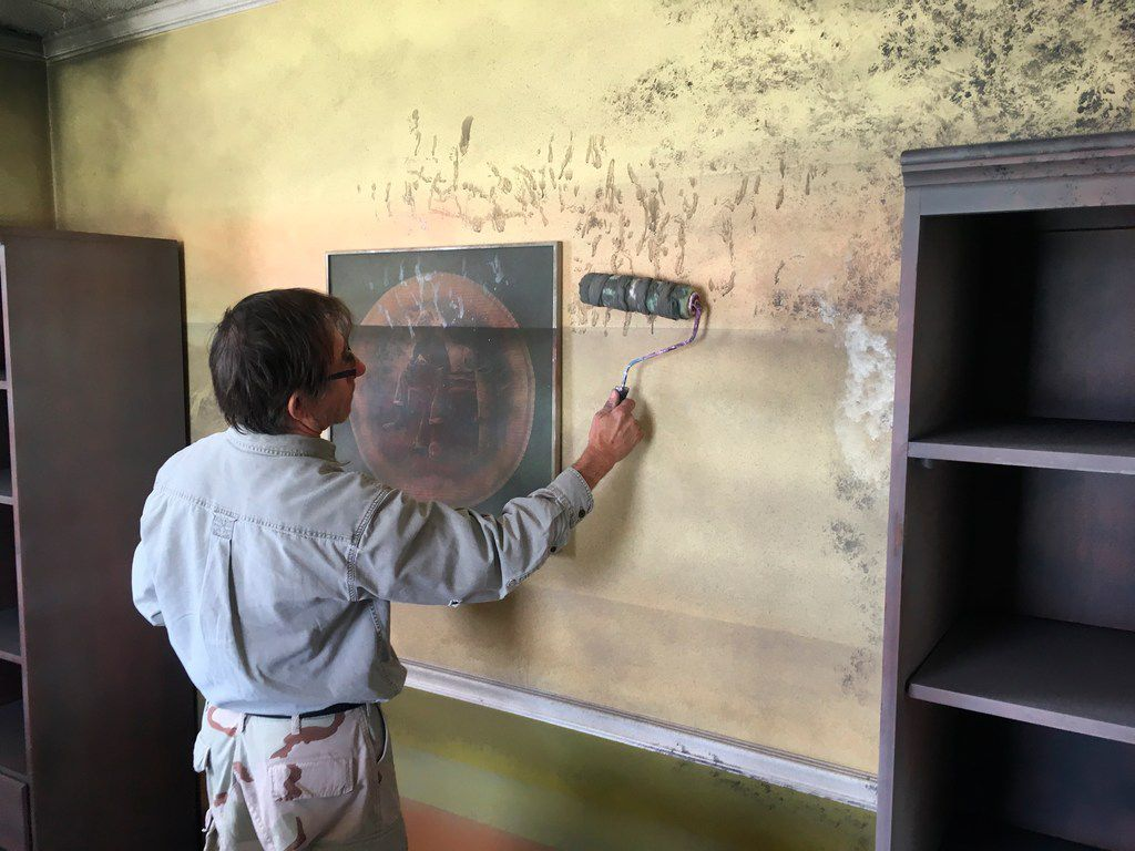 Artist Ken Conner paints mold on the walls of the Flooded House Museum in New Orleans.