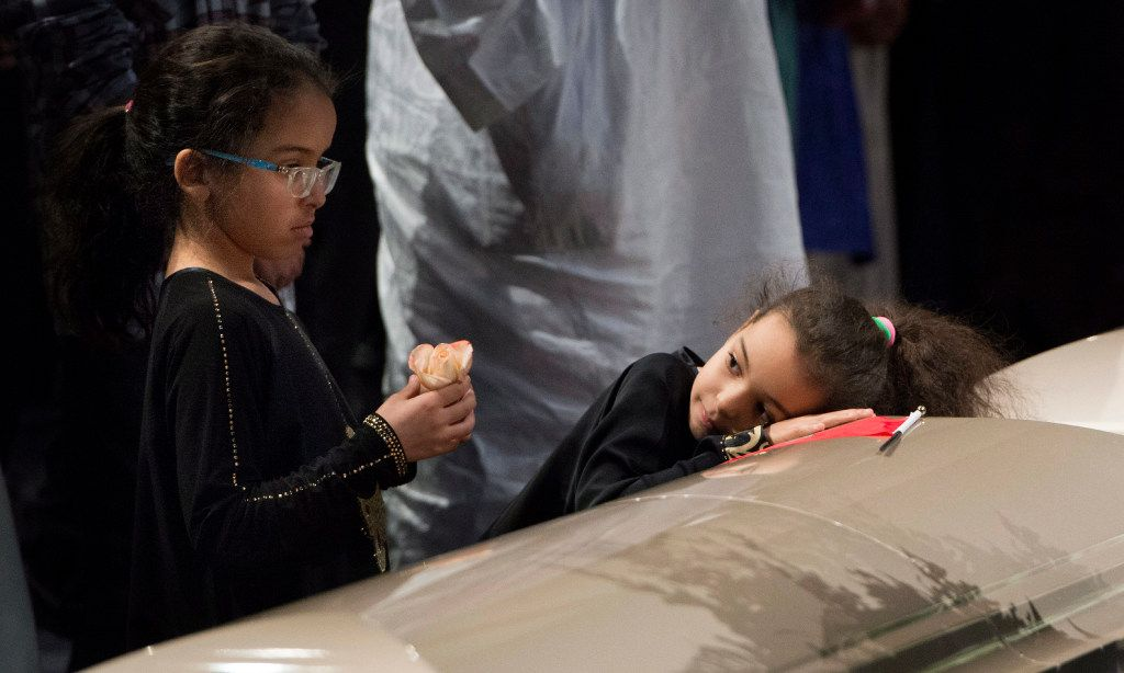 Two young girls reflect next to a casket of one of the six victims of the Quebec City mosque shooting during a ceremony Friday, Feb. 3, 2017, in Quebec City. (Paul Chiasson/The Canadian Press via AP)