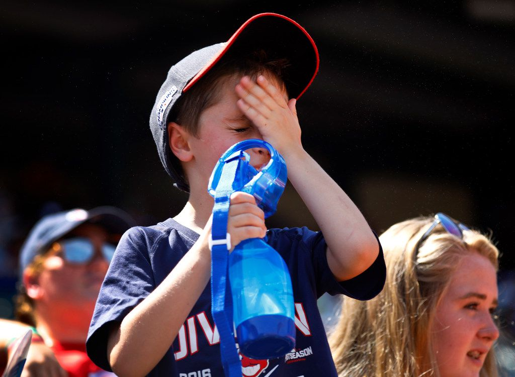 Cleveland Indians fan Brayden Adams, 6, of Southlake, Texas wipes water from his face as he cools himself with a fan at Globe Life Park in Arlington on July 22, 2018.  By the end of the game the temperature was 108 degrees. The Rangers won, 5-0. (Tom Fox/The Dallas Morning News)