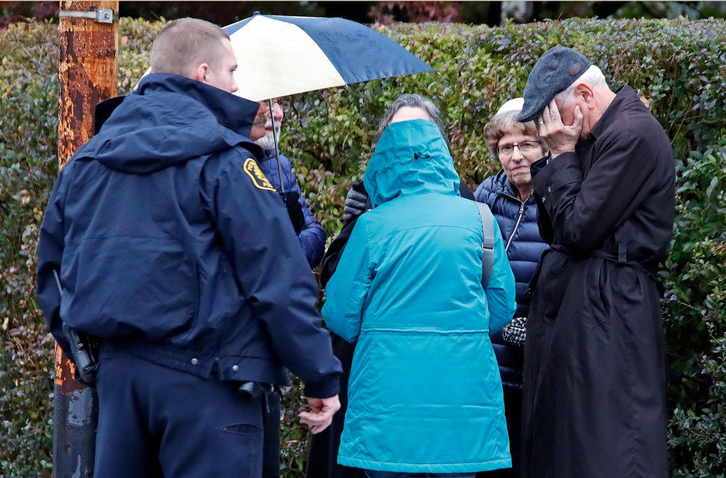 People gather on a corner near the Tree of Life Synagogue in Pittsburgh, Pa., where a shooter opened fire Saturday, Oct. 27, 2018, injuring multiple people. (AP Photo/Gene J. Puskar)