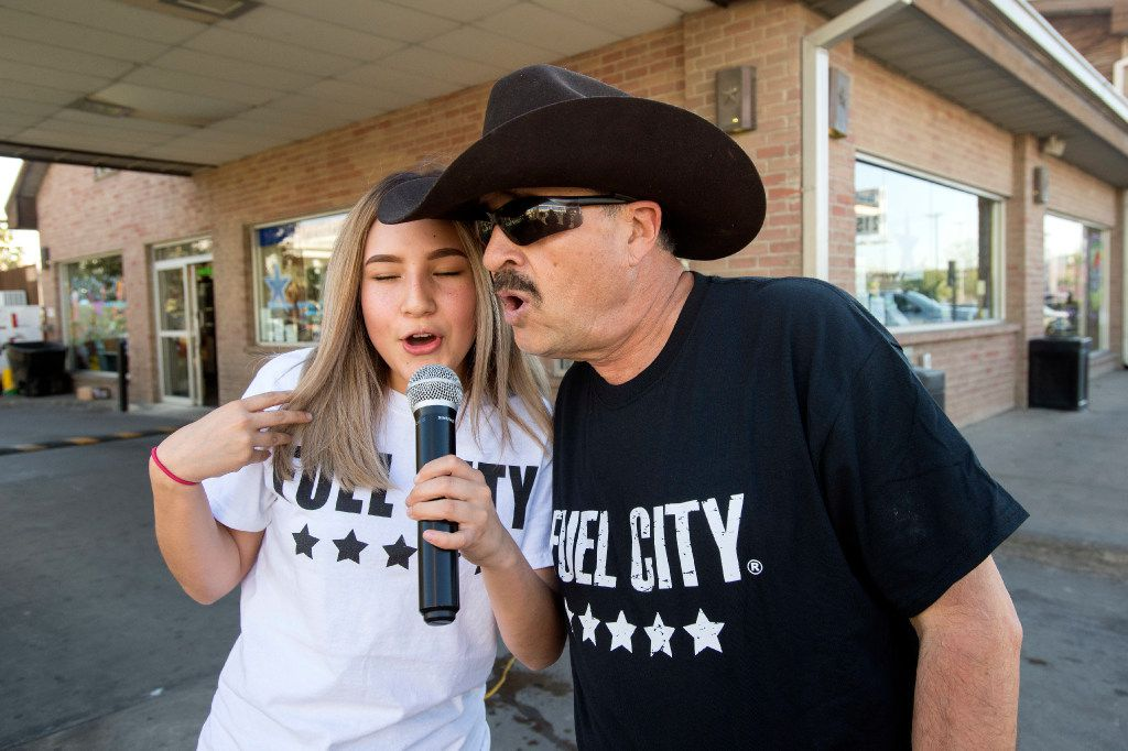 Yamileta Caudillo, left, and Raul Ruvio sing karaoke in the parking lot of the Fuel City truck stopin Dallas. Ruvio has been hosting karaoke at the truck stop every Friday and Saturday night for ten years.  (Jeffrey McWhorter/Special Contributor)