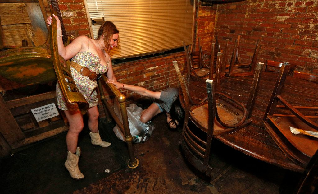 Ashley Barber (left) helps Holly Terry up as they flip the chairs and clean up after closing at the Elbow Room in Dallas on April 16, 2017. (Nathan Hunsinger/The Dallas Morning News)