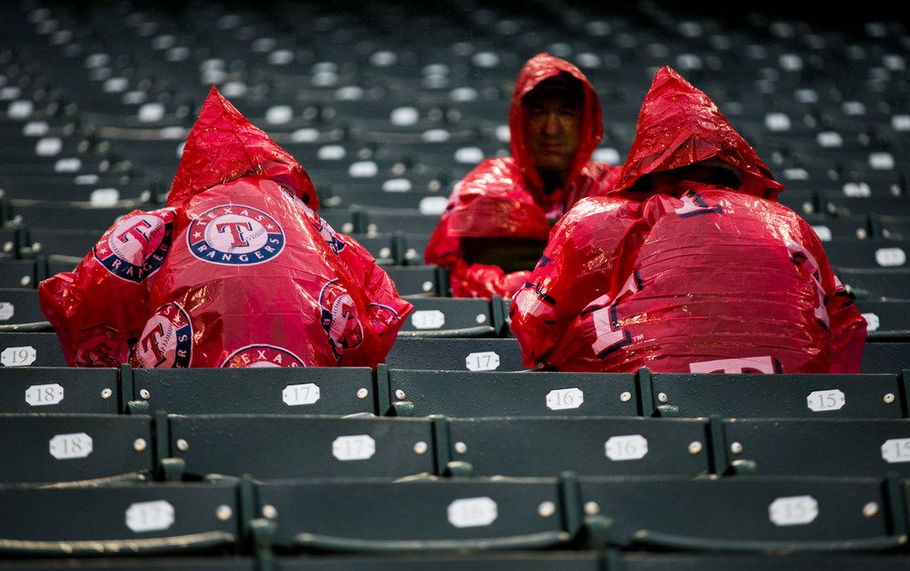 Texas Rangers fans wait in the rain before an MLB game between the Texas Rangers and the Oakland Athletics on Saturday, April 13, 2019 at Globe Life Park in Arlington, Texas. (Ashley Landis/The Dallas Morning News)