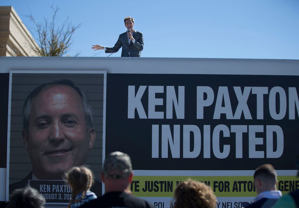 Justin Nelson, who is attempting to unseat Texas Attorney General Ken Paxton, speaks to a small crowd from on top of a billboard truck featuring a booking photo of Paxton and a messages about his indictment, during Nelson's campaign rally at the Rockwall County Courthouse in Rockwall, Texas on Sunday, November 4, 2018. Paxton is still under indictment, having pleaded not guilty to two felony counts of securities fraud.