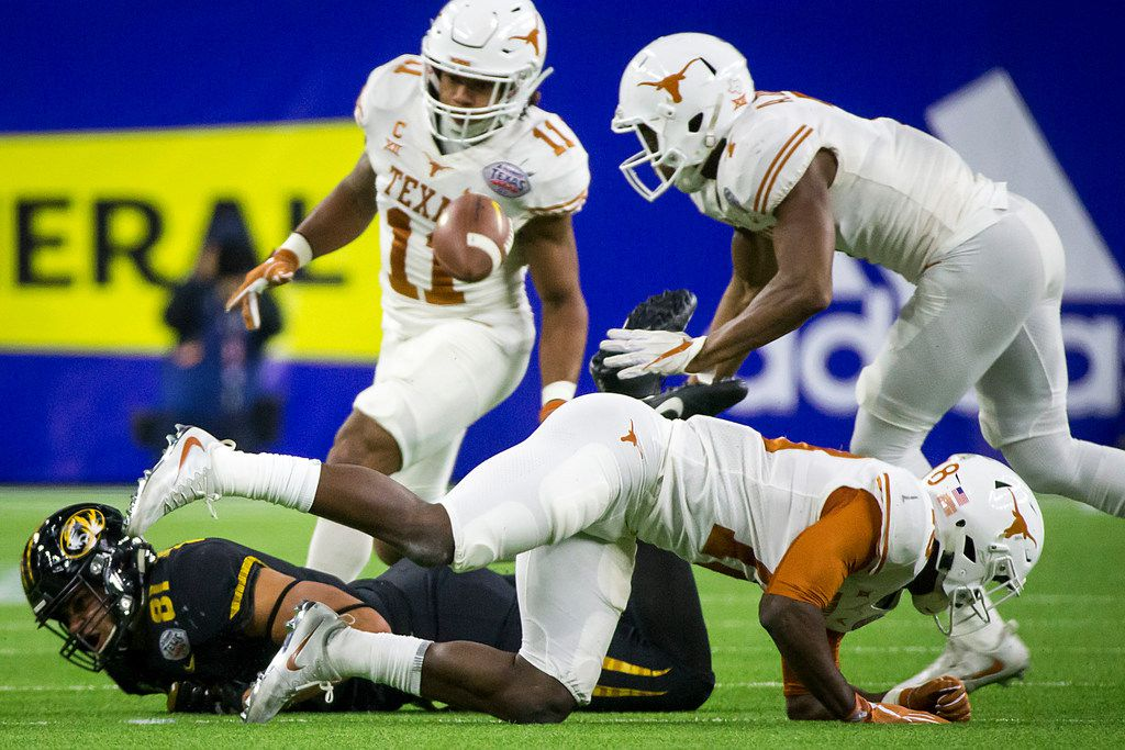 Missouri tight end Albert Okwuegbunam (81) fumbles after a hit from Texas defensive back Davante Davis (18) during the second quarter of the Texas Bowl on Wednesday, Dec. 27, 2017, in Houston. Texas recovered the fumble. (Smiley N. Pool/The Dallas Morning News)