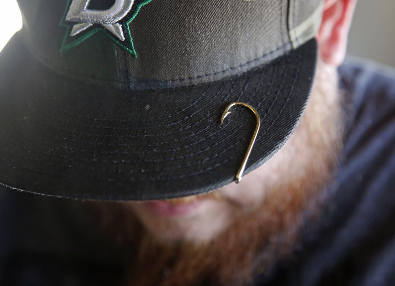 Brian Clark sports a fishhook on the brim of his cap. Clark bought Fisherman's Supply near Lake Ray Hubbard last year and renamed it Clark's Tackle Box.