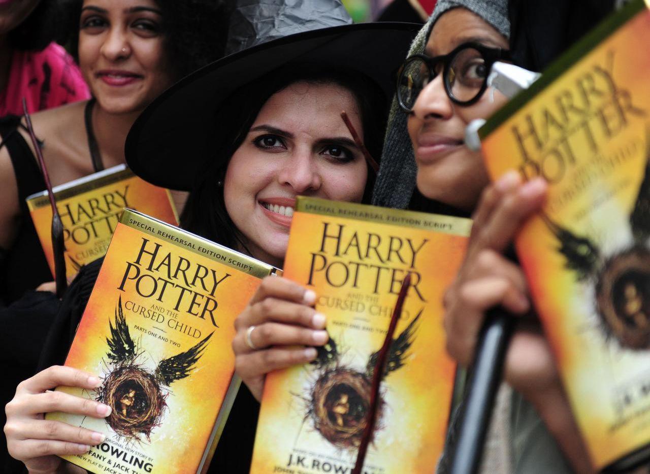 """Seguidores de la saga Harry Potter posan con las copias recién adquiridas del nuevo libro """"Harry Potter and the Cursed Child' el domingo, el día de su lanzamiento mundial. (AFP/GETTY IMAGES/ARUN SANKAR)"""
