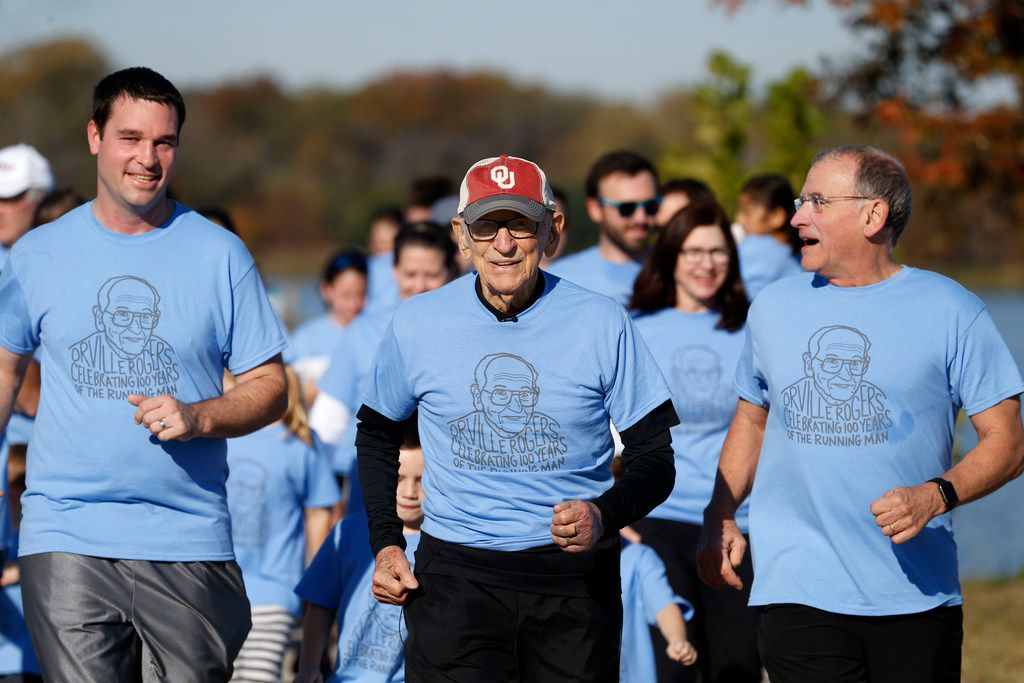 Orville Rogers (middle), who is turning 100 years old, ran with his family including his grandson-in-law Neal Anthony (left) and son Rick Rogers (right) near White Rock Lake in Dallas on Saturday. Orville's  family members ran a collective 100 miles that morning and finished the last mile with him. (Rose Baca/Staff Photographer)