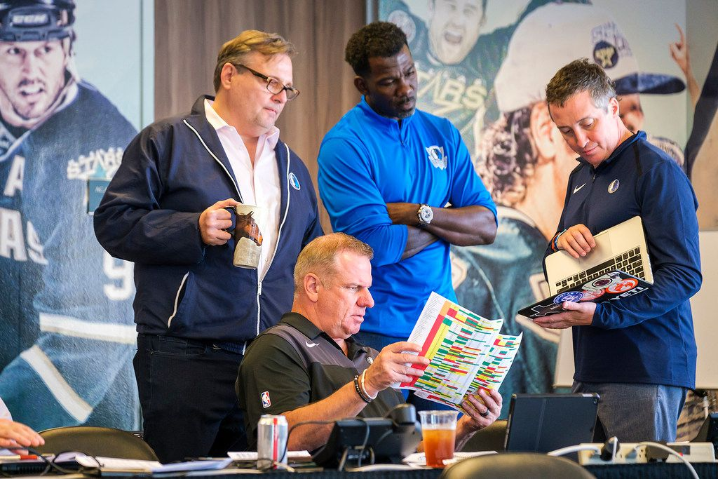 Dallas Mavericks President Donnie Nelson, left, confers with Tony Ranzone, seated, director of player personnel; Michael Finley, center, vice president of basketball operations; and Casey Smith, head athletic trainer, on Thursday, June 20, 2019, in Dallas about the NBA basketball draft, which was about to start. (Smiley N. Pool/The Dallas Morning News via AP)