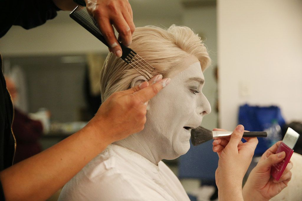Wig technician Michael Briseno places a wig on Ben Bryant, who continues to apply his black-and-white makeup.