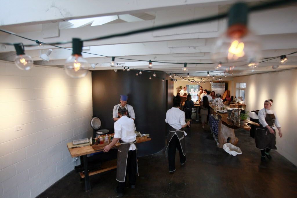 Sushi chefs, left, prepare food inside the pop-up location for Uchi restaurant during a preview dinner.