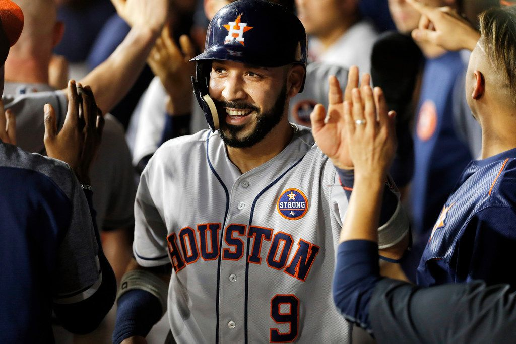 ARLINGTON, TX - SEPT 25: Marwin Gonzalez #9 of the Houston Astros is congratulated by teammates after scoring on a two RBI double hit by Evan Gattis #11during the fourth inning of a baseball game against the Texas Rangers at Globe Life Park September 25, 2017 in Arlington, Texas. (Photo by Brandon Wade/Getty Images)