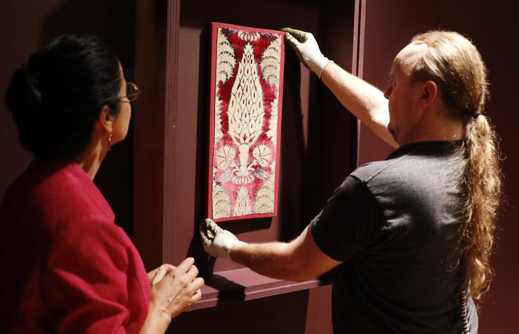 """Doug Velek, of the Dallas Museum of Art, right, installs a textile from Asia, late 16th, early 17th century as Dr. Sabiha Al Khemir, the DMA's Senior Adviser for Islamic Art and the curator of the exhibition, oversaw the installation of the """"Spirit and Matter, Masterpieces from the Keir Collection of Islamic Art"""" at the DMA on Wednesday, Sept. 9, 2015. The exhibition presents a selection of more than 50 masterworks in various mediums and explores 13 centuries of Islamic art making across 3 continents, from Spain to Central Asia. (David Woo/The Dallas Morning News)"""