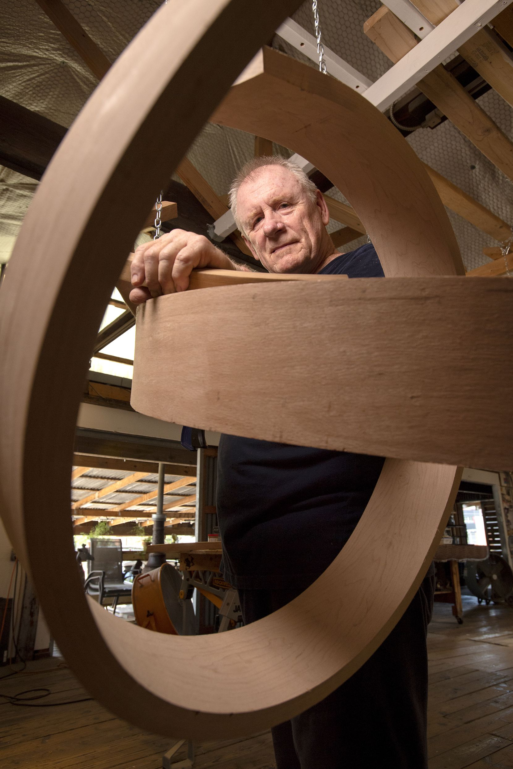 Wood sculptor Rick Maxwell poses with an unfinished sculpture.